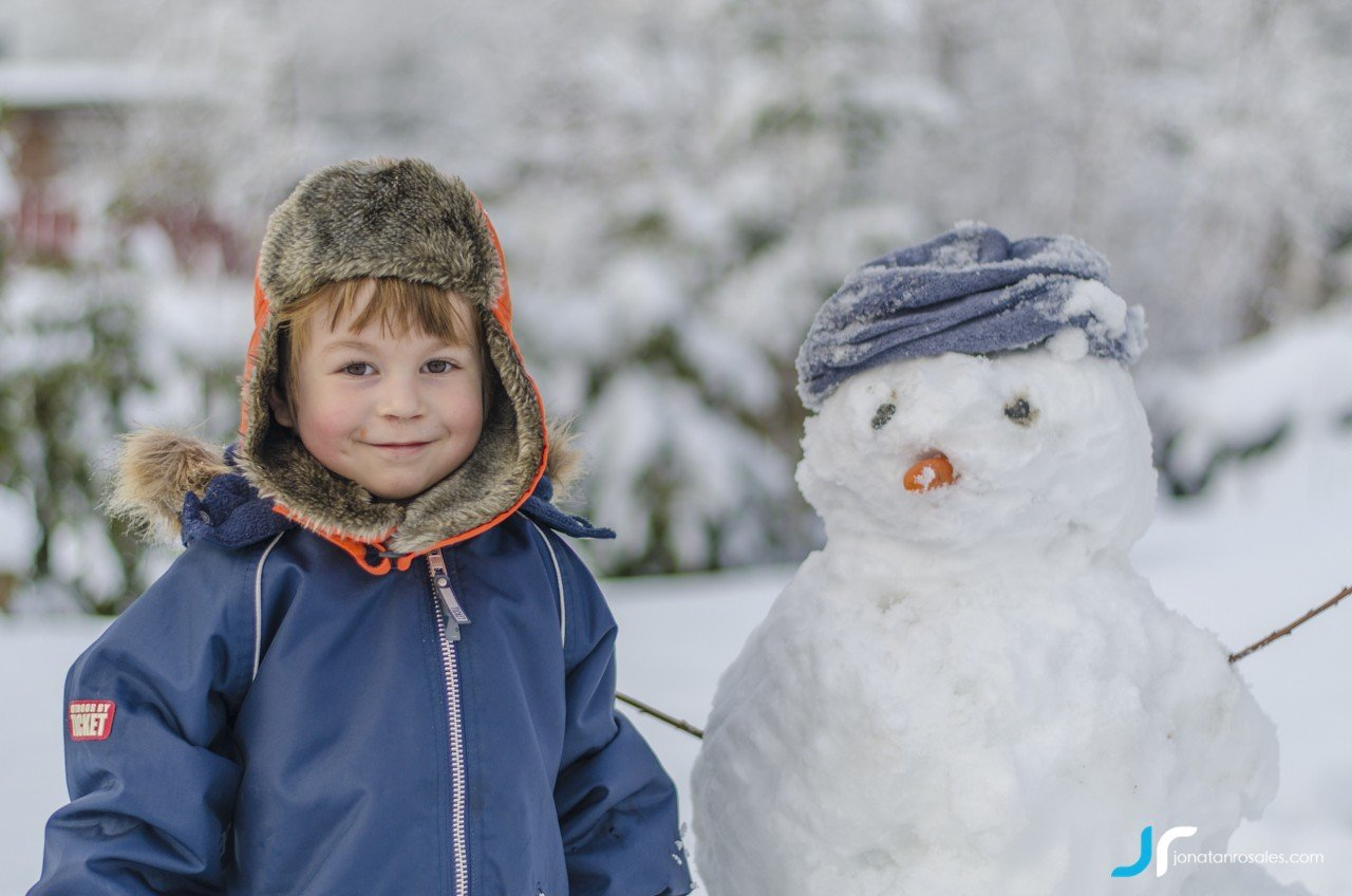 cute boy smiling with snowman